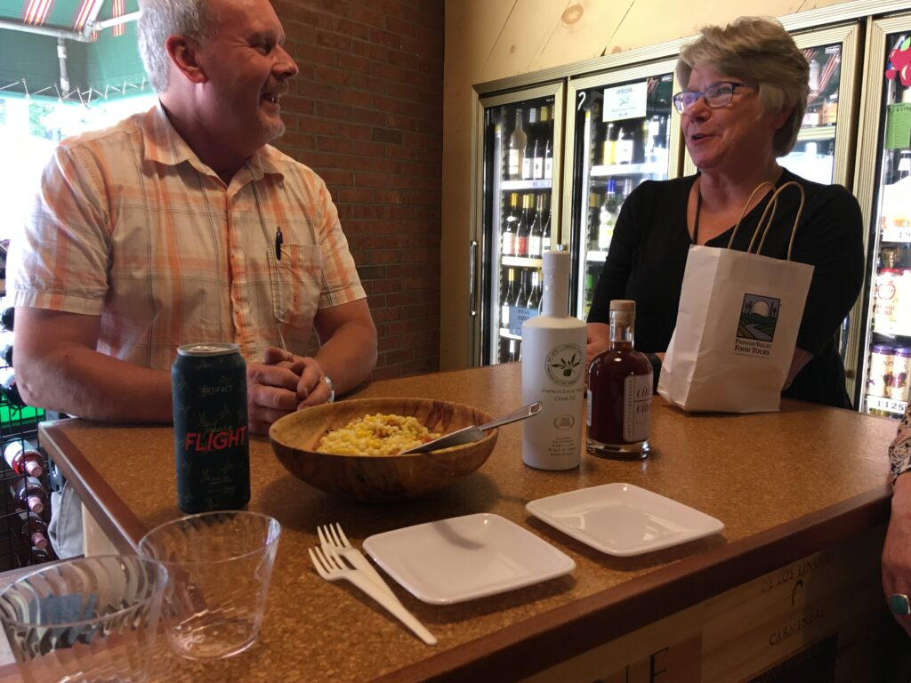 Shop owner serves local cider and salad